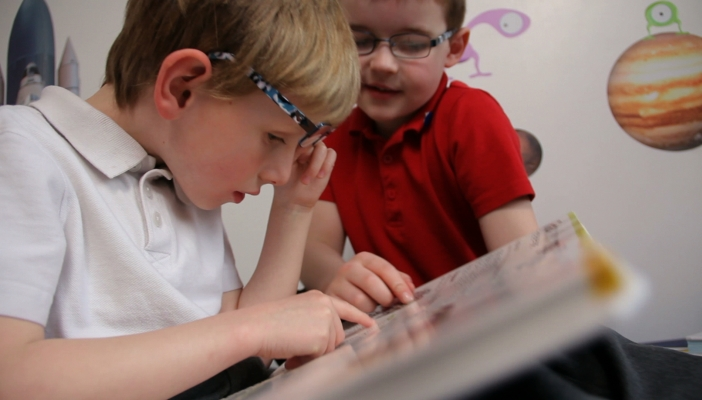 Two boys reading a DK Braille book
