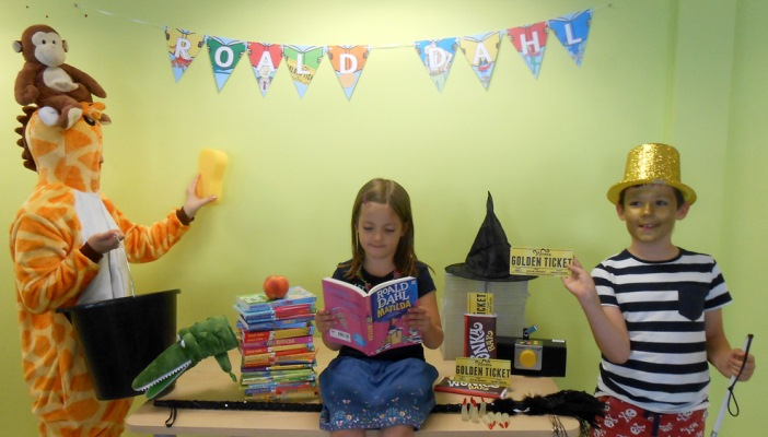 Three kids reading Rold Dahl books