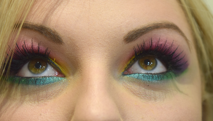 A selfie closeup of a woman's eyes wearing bright multi-coloured eye makeup.