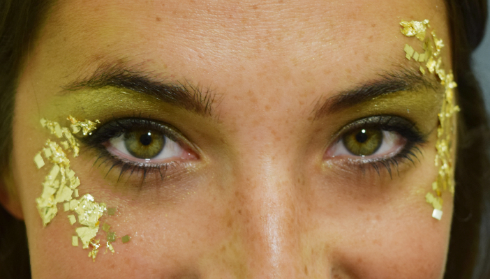 An eye makeup selfie with gold leaf decorating the outer edges of each eye.