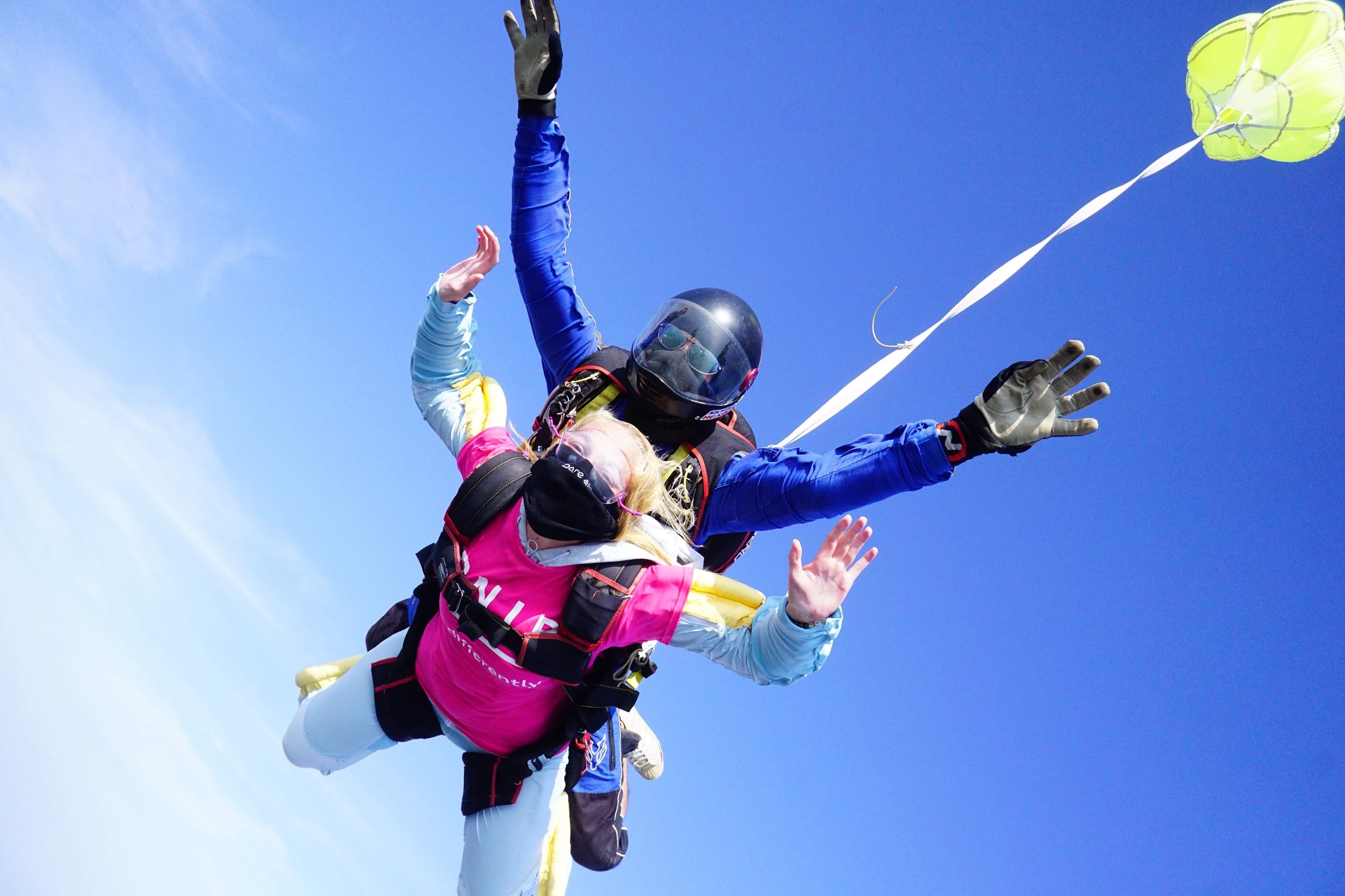 Daisy mid sky dive with her arms outstretched whilst wearing a mask