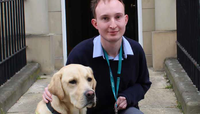 Darrel Drury sits on the steps with his guide dog