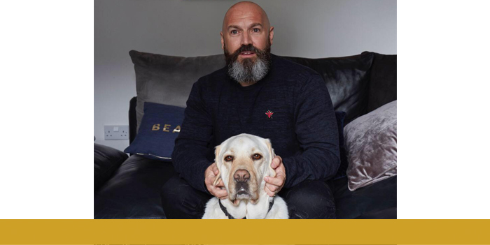 Dave Steele sits on a sofa stroking the ears of a yellow Labrador sat in front of him
