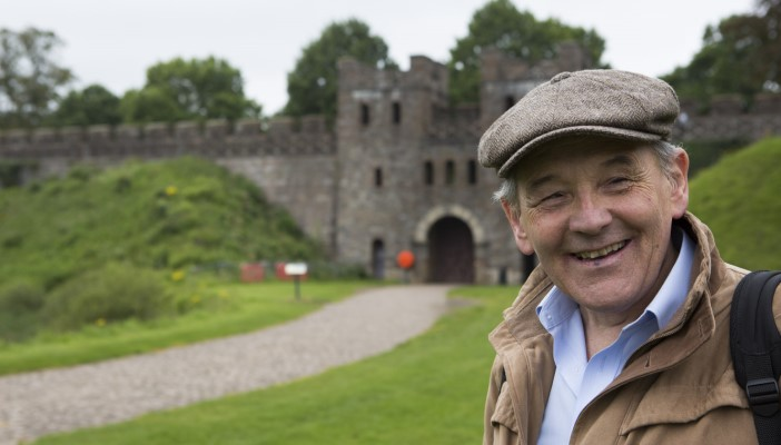 Des looks at the camera and smiles with an historic castle out of focus in the background