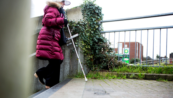 Photo of person walking with long cane