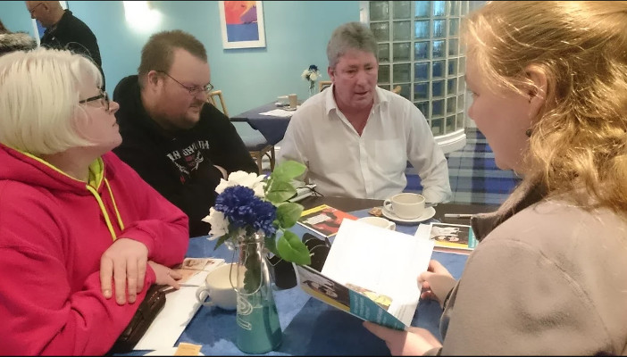 Image shows members of the Social Eyes group at table in discussion.