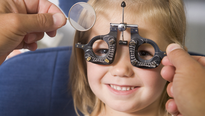 Young child smiling while having an eye test