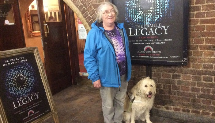 Eleanor Burke with her guide dog Ava standing in front of the Charing Cross Theatre in London