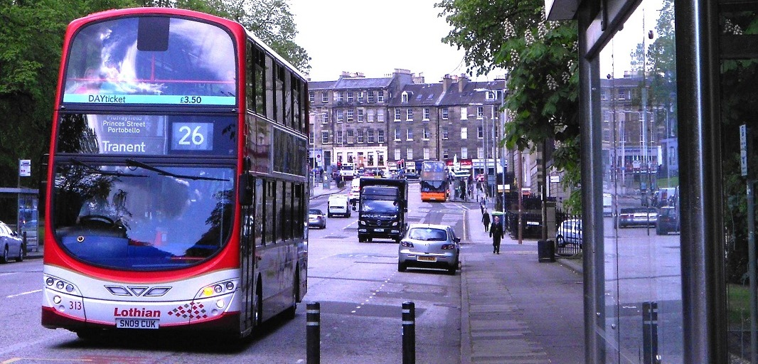 Image of a number 26 bus to Tranent driving towards a bus stop with cars, another bus and truck in the background