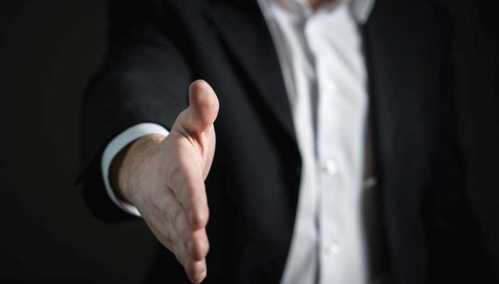 Photo of a man in a suit reaching out to shake hands