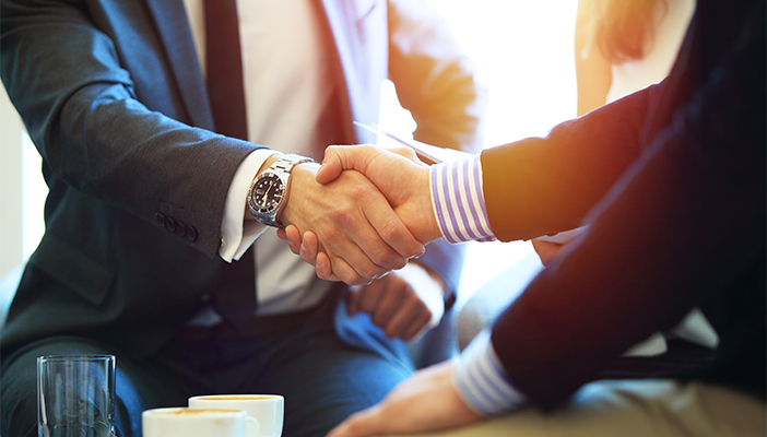 Two men in suits shake hands across a coffee table