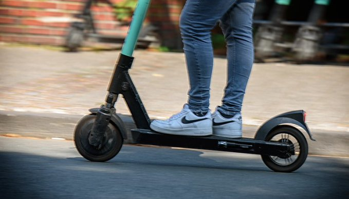 A scooter with a person riding it (only the legs of the person is shown) with a blurred image of other scooters in the background to give the impression of movement.