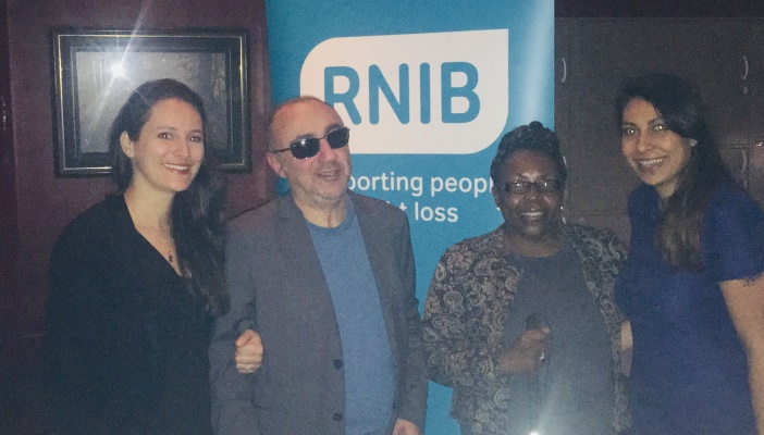 Image shows four people, including Shadeen Rose at the dine in the dark event with an RNIB banner in the background