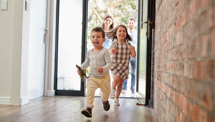 Two children running into a house with parents coming in behind them