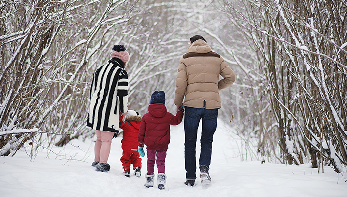 Parents and two children walking through a forest covered in snow