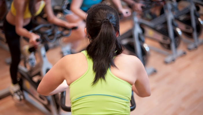 Photo of fitness instructor facing a cycling class