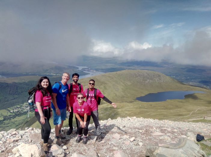 Five RNIB trekkers posing on rocky path with mountainous background