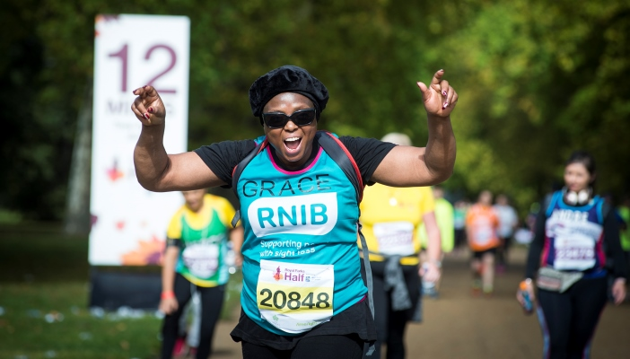 Grace Imina looking thrilled with arms in the air running past mile 12.