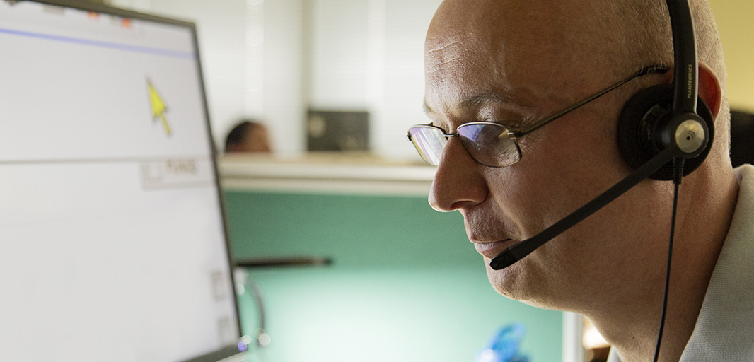 Helpline and sight loss adviser with a headset in front of computer screen