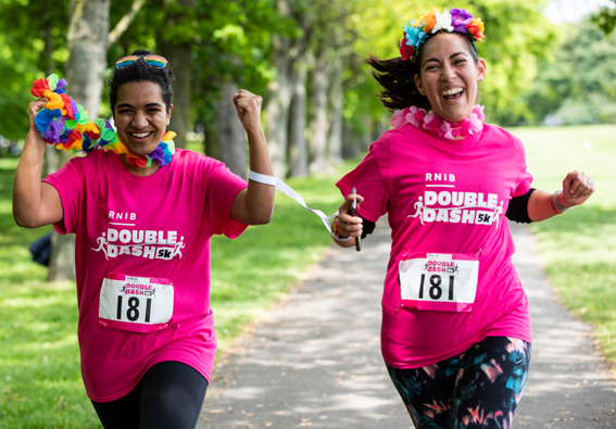 Two Double Dash runners, smiling with flowers round them