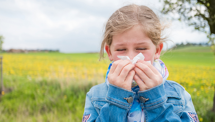 Girl with hayfever holding tissue to her nose