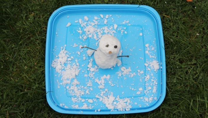 Snowman sitting on blue container lid