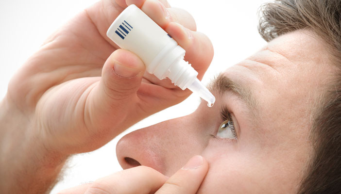 Man administering eye drops