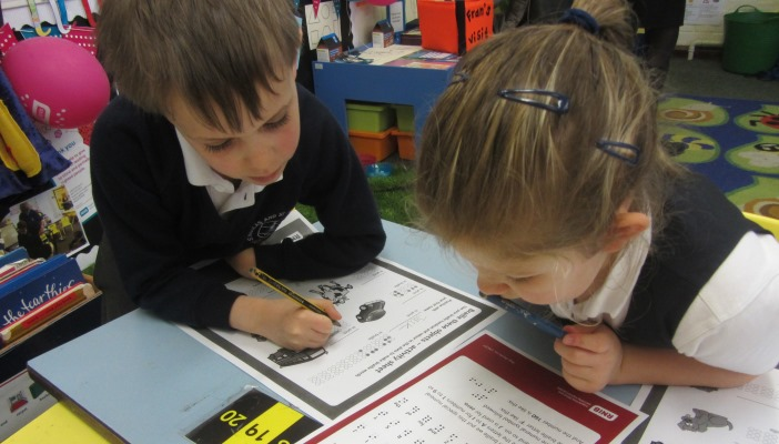 Children completing braille activity sheets
