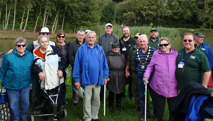 Image shows a group photo of the Deafblind fishing group, with a mix of members and coaches