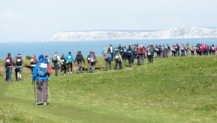 Image shows a group of several people trekking with a scenic backdrop of cliffs and the sea