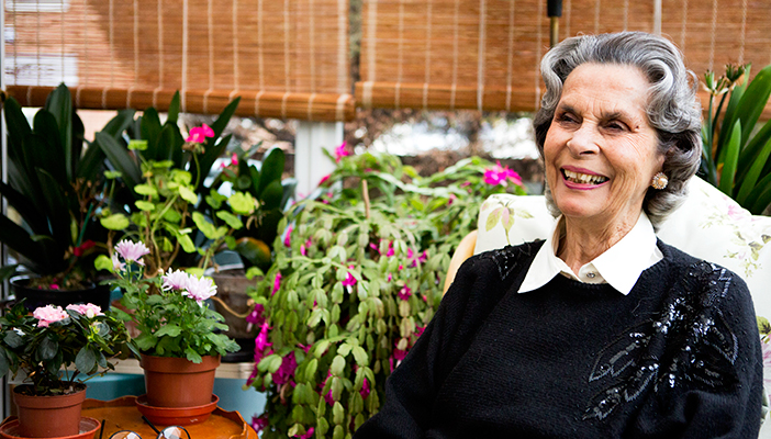 A picture of a smiling woman, surrounded by plants.