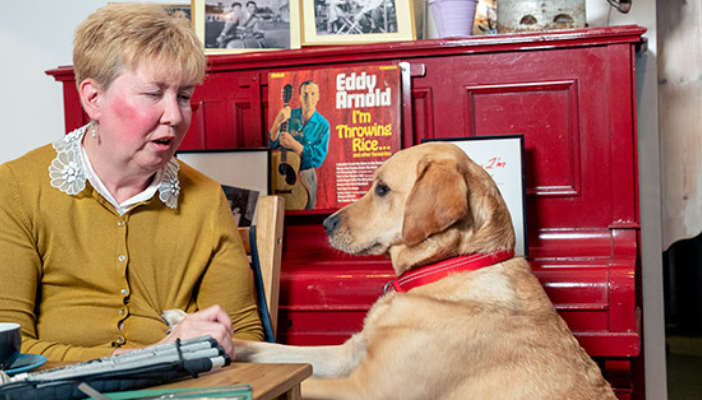 A woman and her guide dog in a cafe