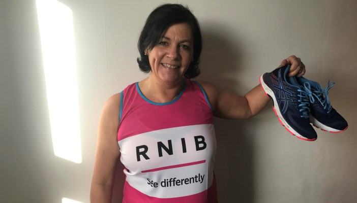 Jeanine Levers holding her running shoes wearing a Team RNIB vest