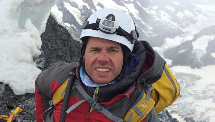 Photo of John Churcher in climbing gear standing on a snowy mountain