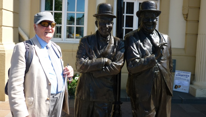 Image shows John on a train trip to Ulverston, standing next to the statue of Oliver and Hardy.