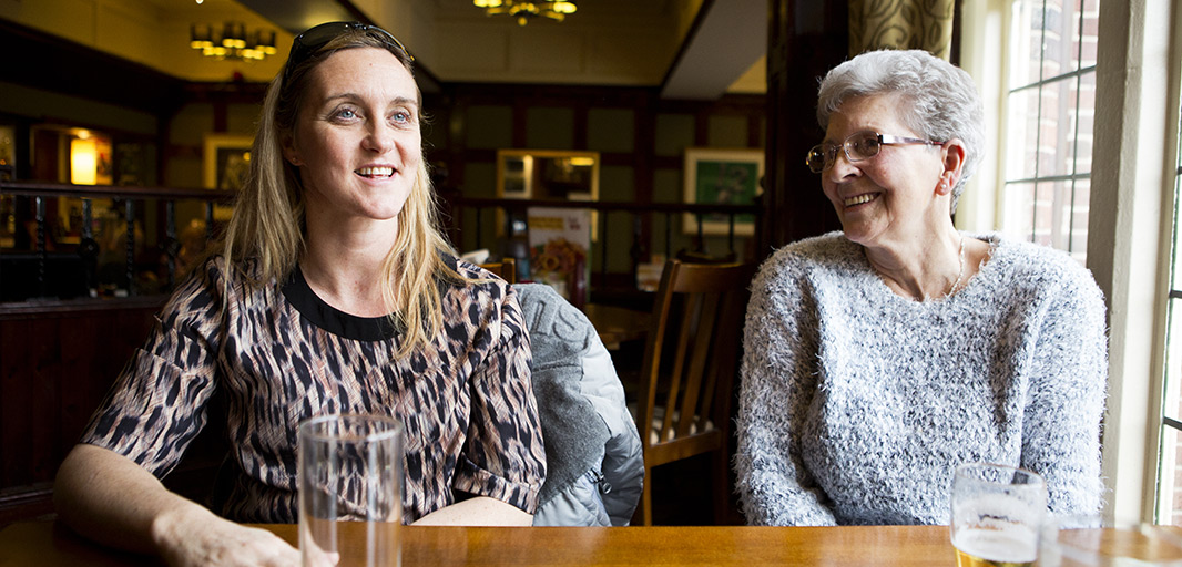 Two women of different ages enjoying drinks and company in a pub