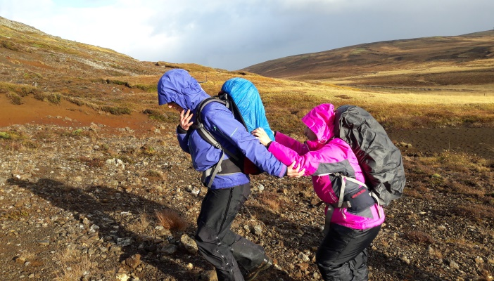 Image shows someone being guided on rocky terrain holding on to a guides backpack