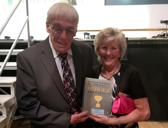 Keith standing with his wife Carol, holding the award.