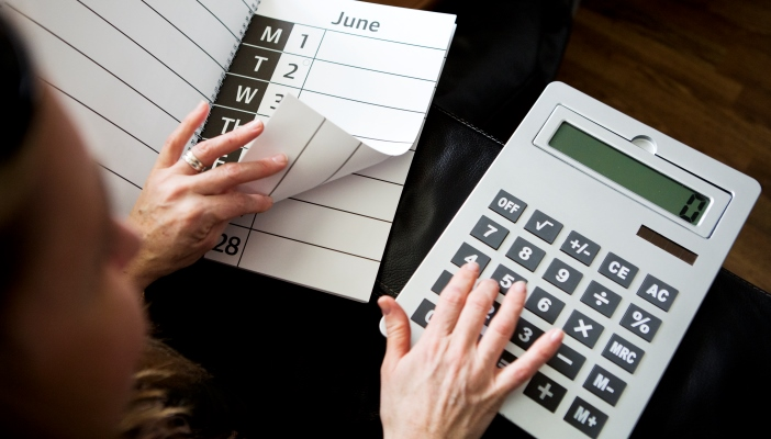 Woman using a large print calendar and calculator