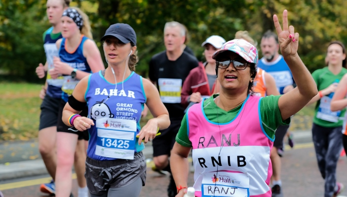 RNIB runner running past the cheer point and giving a peace sign