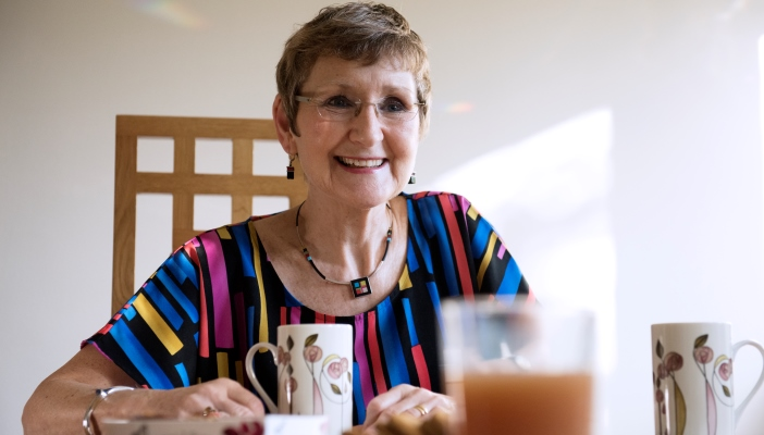 An older lady having a cup of tea with company