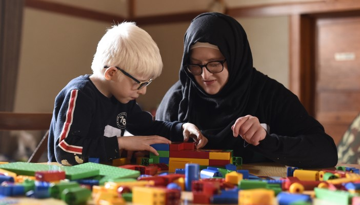 A child and adult play with multicoloured building blocks.