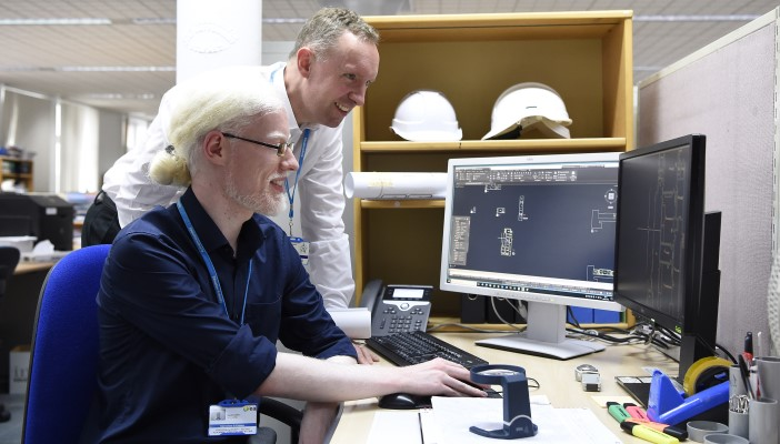 Two employees look at computer screens together