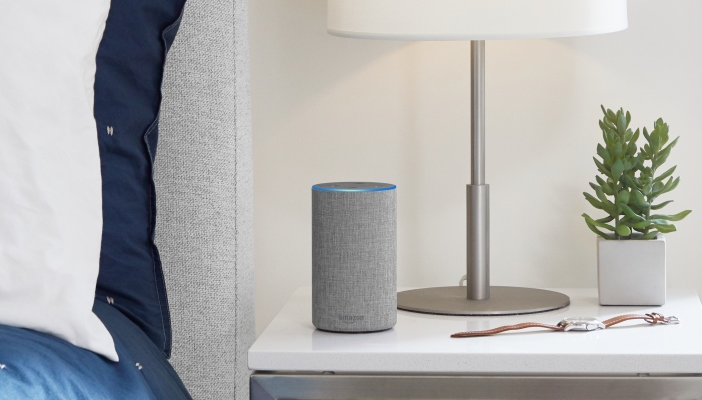 Image shows a grey Amazon Echo on a white nightstand. There is also a plant, lamp and watch on the nightstand.