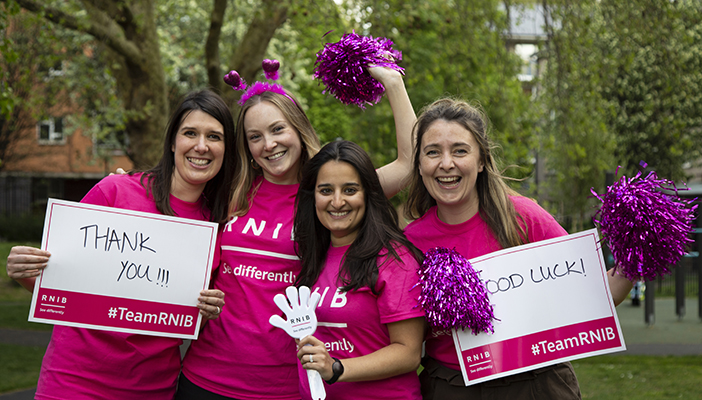 Four women in pink RNIB t-shirts smiling and holding signs saying Thank you and Good luck