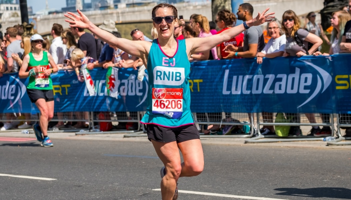 Image shows a girl called Emma running the London Marathon with a smile on her face and runners all around her.