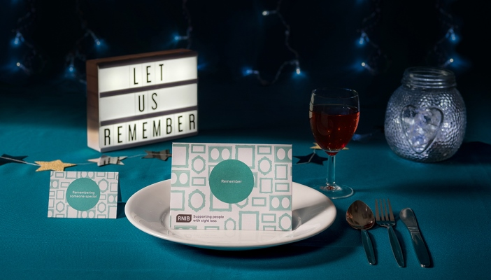 Image shows a donate in memory place card on a table with cutlery and a drink, with a sign in the back saying 'let us remember'