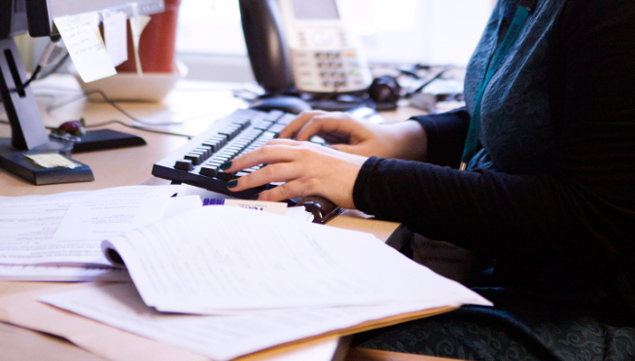Image of person typing on computer keyboard with open books on the table