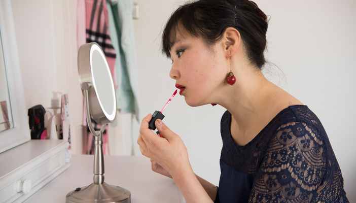 Woman putting on lipstick using a small mirror