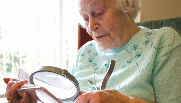 Elderly lady reads with a magnifying glass